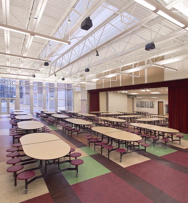 Interior of a middle school's multi purpose area. This serves as a cafeteria and a folding wall at the left opens to reveal the gym.