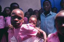 Uganda Africa, children with adult responsibility a child cares for a baby.